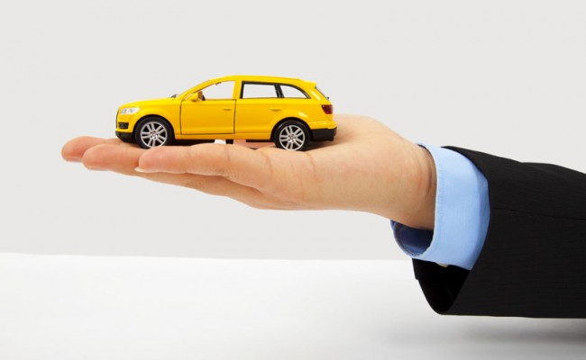 Businessman's hand holding a car